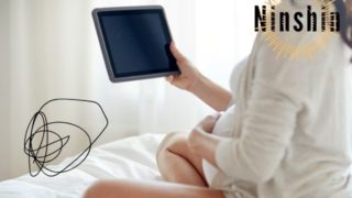妊婦がベッドの上でタブレット見ている