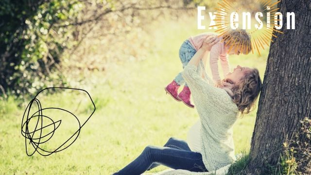 公園で母が赤ちゃんを抱き上げている